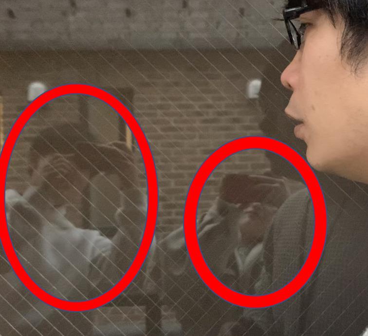 窓ガラスにスマホで写真を撮る人が写っている写真