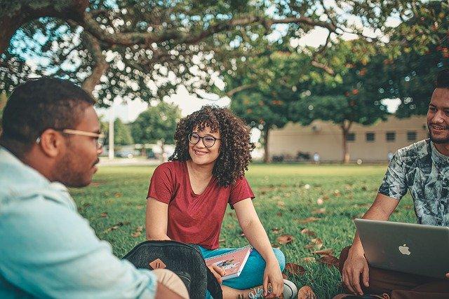 芝生で談笑する大学生