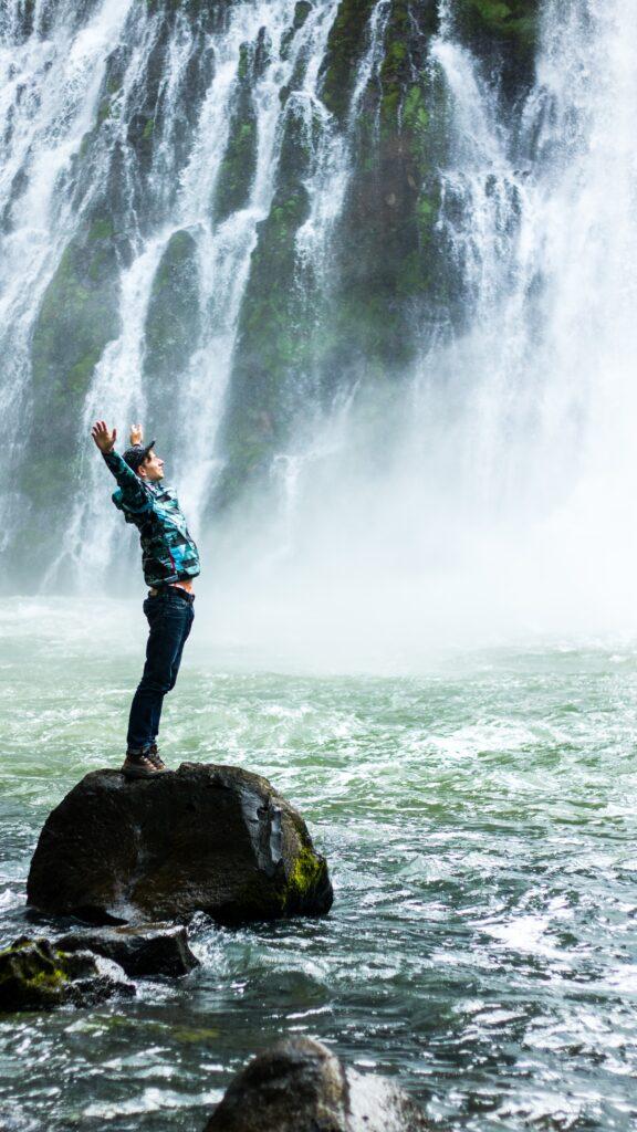 男性が滝を見ながら両手を挙げてる画像